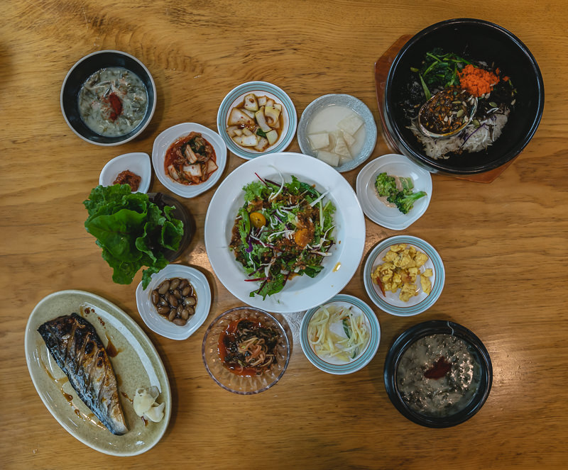 A top down view of lunch at Kang Chef's, consisting of grilled mackerel, abalone bibimbap and lots of sides
