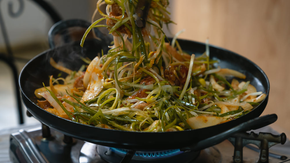 A pork and veggie dish being cooked in a wok style pan on a table top burner