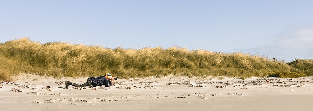 A person lying down on a beach taking a shot with a camera