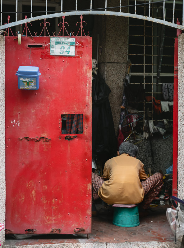 A man working on something in a Tainan backstreet doorway, sitting with his back to us on an upturned bucket