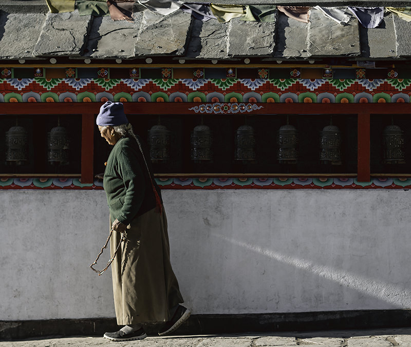 A local taking the time to spin each and every prayer wheel on a long prayer wall in Manang