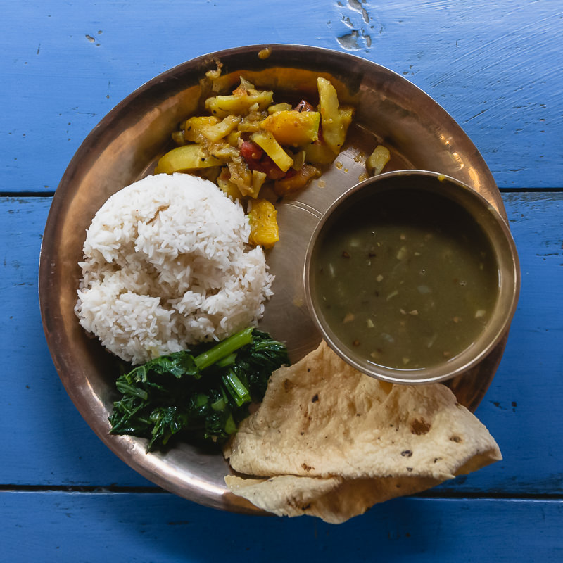 Dal Bhat, the national dish of Nepal, on a copper dish set on a blue wooden table at the Larke Peak Hotel on the Manaslu Trek