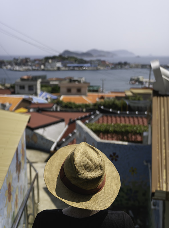 A person looking down over the colourful roofs to the port on Chuja-do