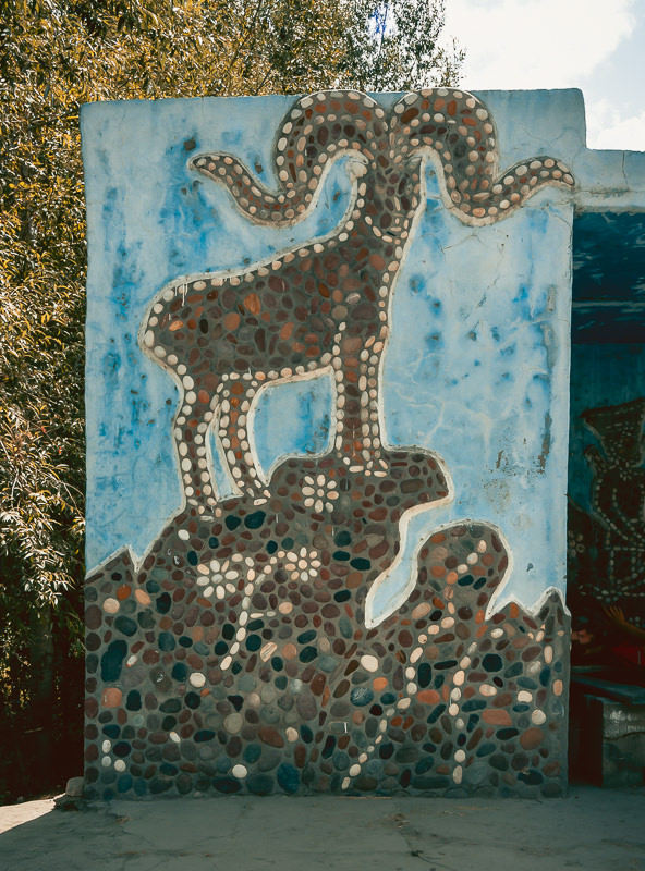 A prominant Marco Polo Sheep on one end of a particularly large and dominant Soviet bus stop on the Pamir Highway in Tajikistan