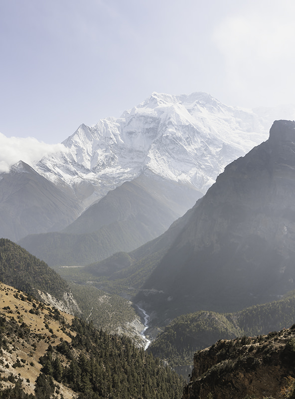 The Marsyangdi a distant silver sliver in the Manang Valley with snowy mountains rising behind