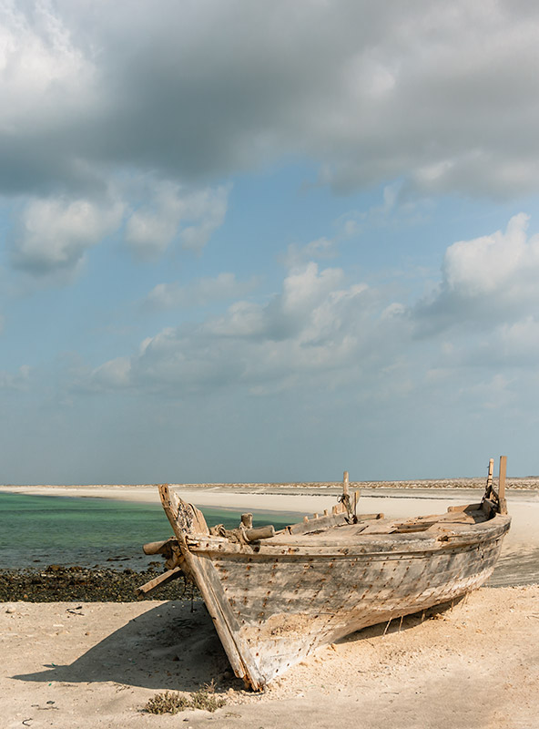 A dilapadated old fishing boat on a sandy beach on Masirah Island in Oman