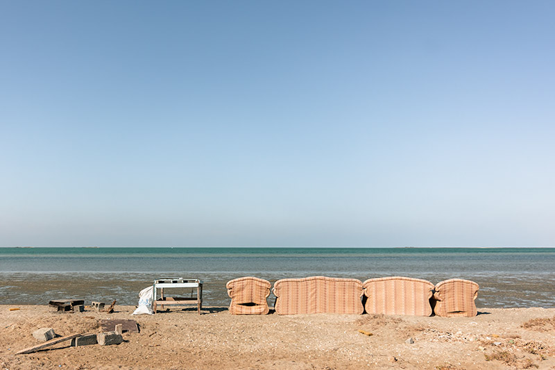 A row of old armchairs sit on the sandy west coast of Masirah Island in Oman, facing the sea