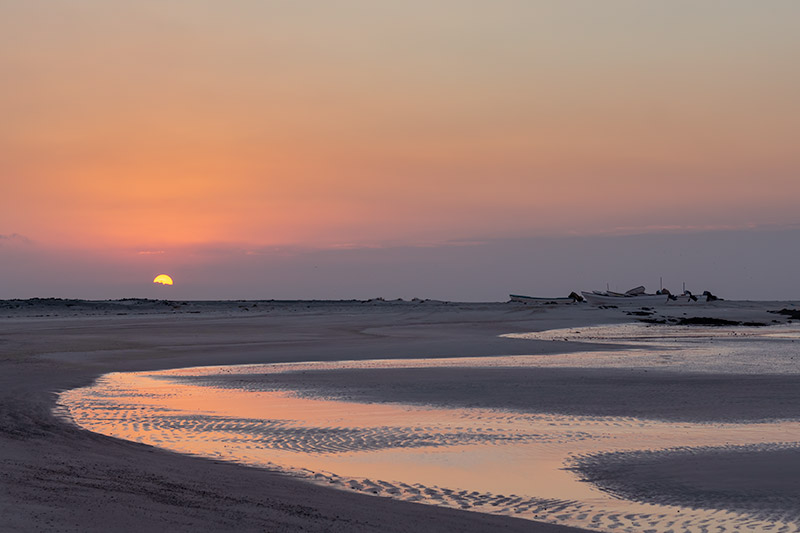 The sun sets on a west oast beach on Masirah Island in Oman, fishing boats sitting above the tide line on the sand