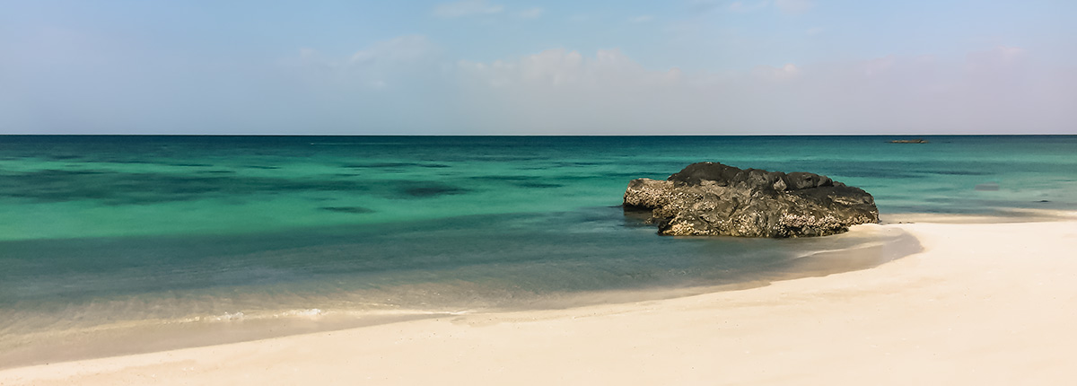 A strip of white sand bordeing turquoise water on the west coast of Masirah Island in Oman