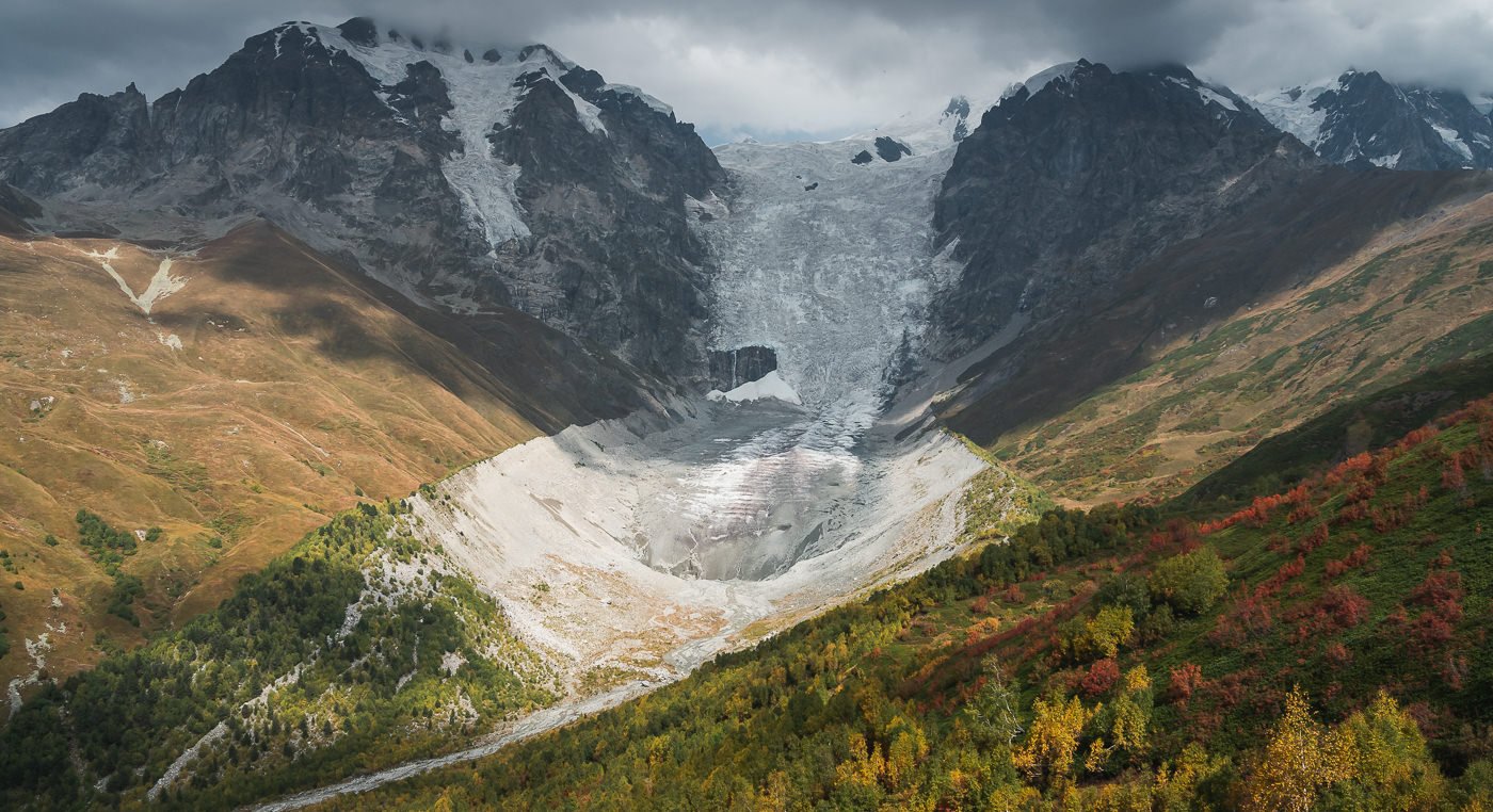 Adishi Glacier under bright sunlight while the mountains above lay under the shadow of heavy clouds, seen from the trail up to Chkhunderi Pass on the Mestia to Ushguli trek