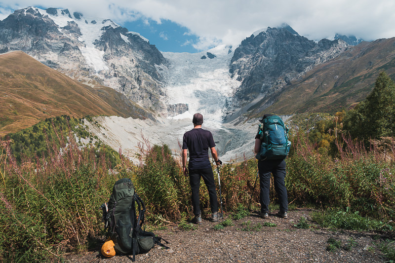Two hikers look across to impressive Adishi Glacier from a viewpoint on the Mestia to Ushguli trek