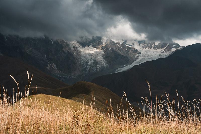 Glaciers and mountains seen under moody skies while the sun shines through, from the ridge above Chkhunderi Pass on the Mestia to Ushguli trek in Svaneti