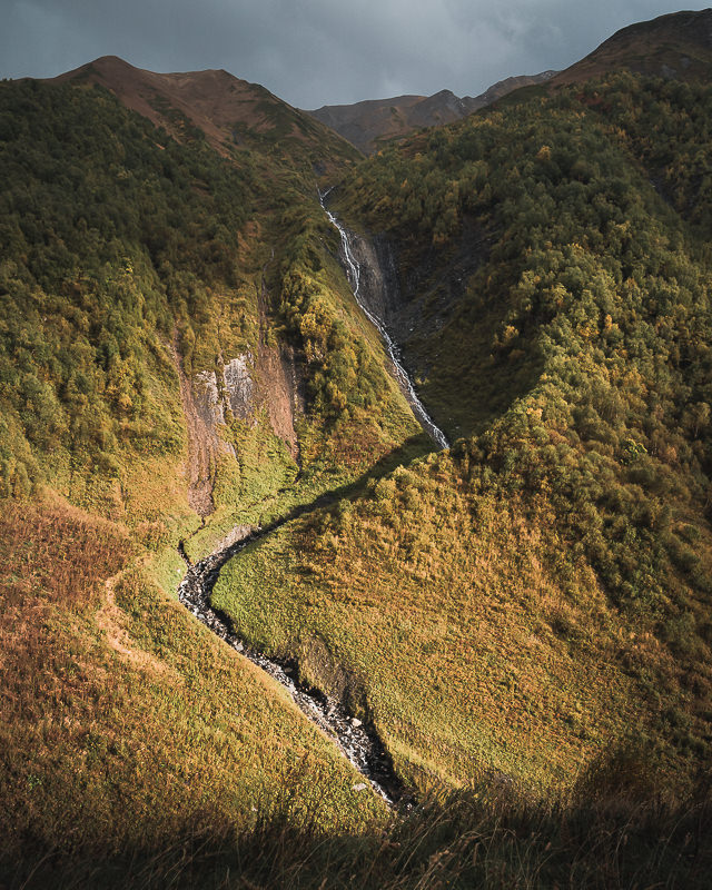 A snaking waterfall is illuminated briefly by the afternoon sun, in the Khaldeschala valley on the Mestia to Ushguli trek