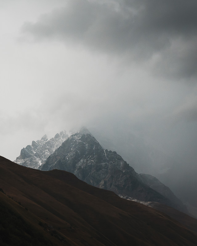 A jagged mountain peak appearing from the mist in the Kaldeschala valley on the Mestia to Ushguli trek