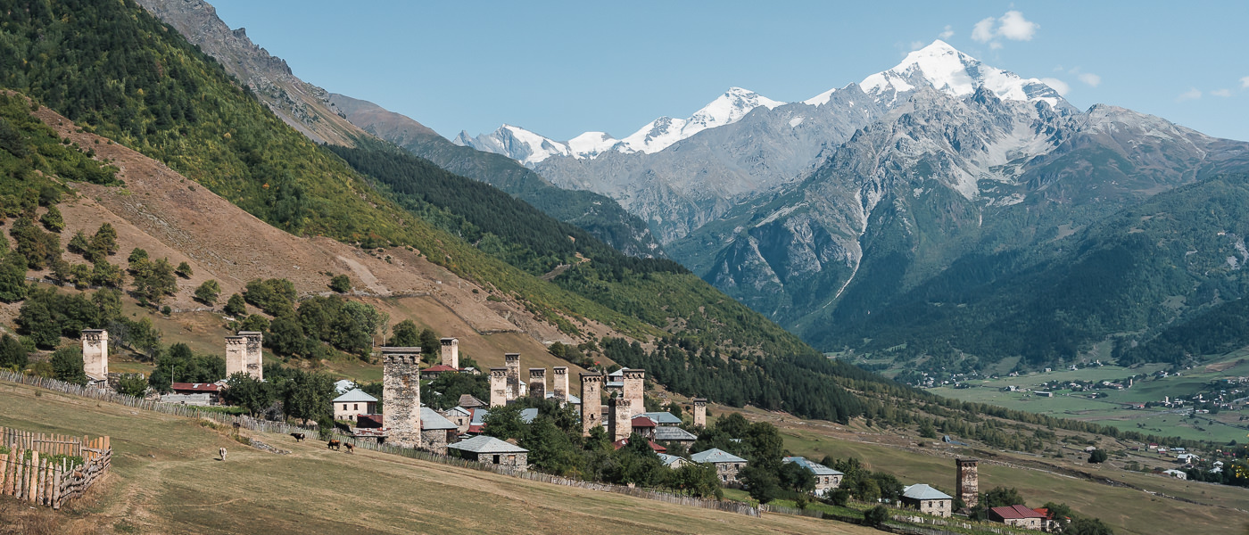 Many traditional Svanetian towers line the hillside in the village of Lakhiri, with Mount Tetnuldi rising behind, seen on the first day of the Mestia to Ushguli section of the Transcaucasian Trail in Svaneti, Georgia