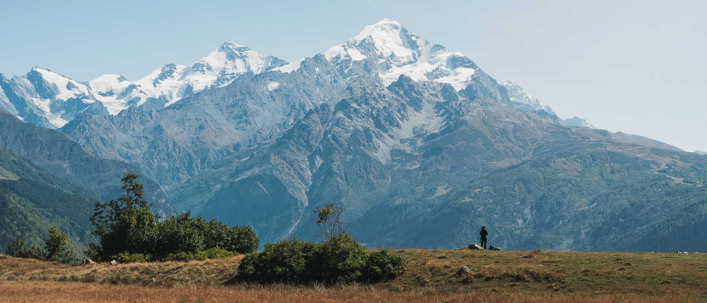 A hiker stands looking towards the pyramidal shape of Mount Tetnuldi at the high point of Day 1 on the Mestia to Ushguli section of the Transcaucasian Trail in Svaneti, Georgia