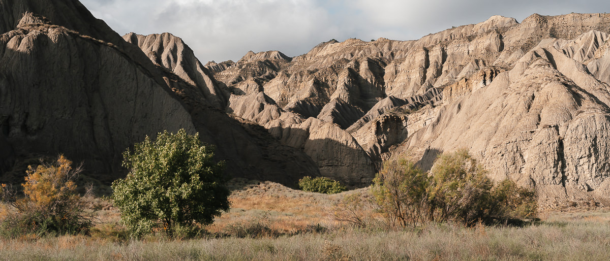 Sandy cliffs and rock pinnacles towering above grassland near Mijniskure in Vashlovani National Park
