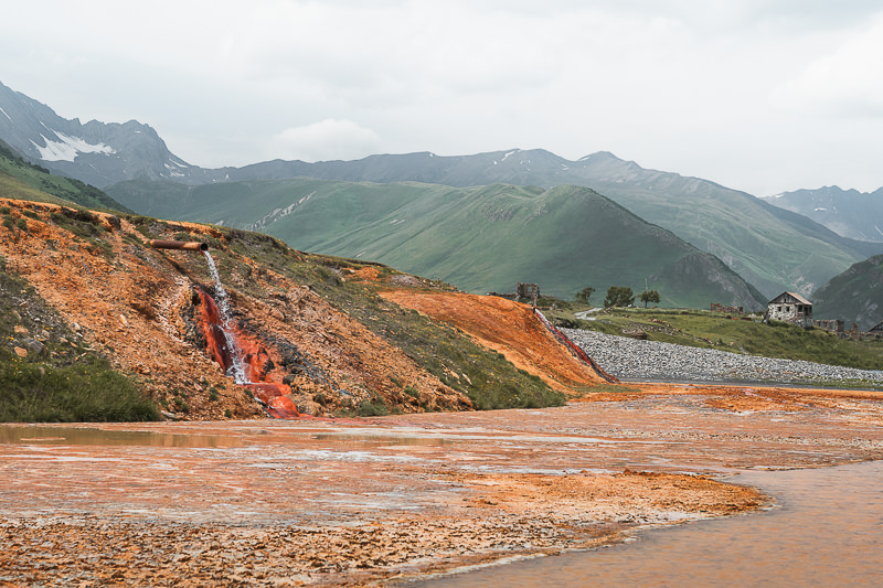 Rich reds and orange mineral deposits surround two gushing pipes on the side of a verge in Truso valley in northern Georgia