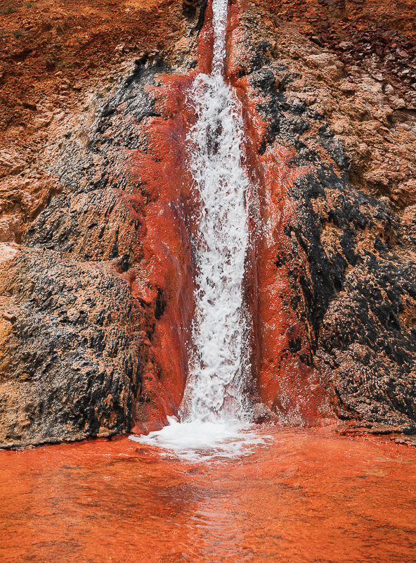 Rich reds and orange mineral deposits surround a gushing pipe in Truso valley in northern Georgia