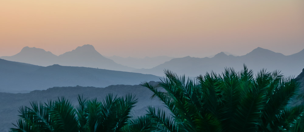 Soft sunset hues over the layered mountains with date palms in the foreground, as seen on a 10 day Oman itinerary