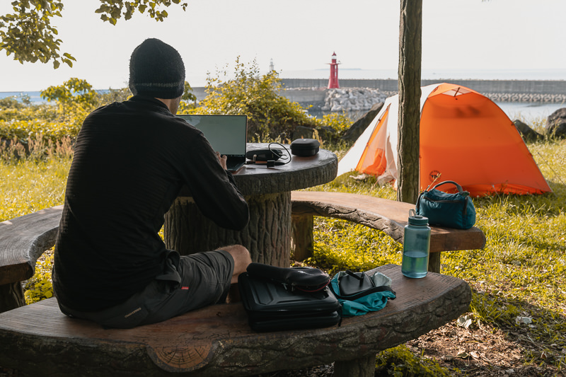 A person working on their laptop at a shaded picnic bench while their tent sits in the sun in front