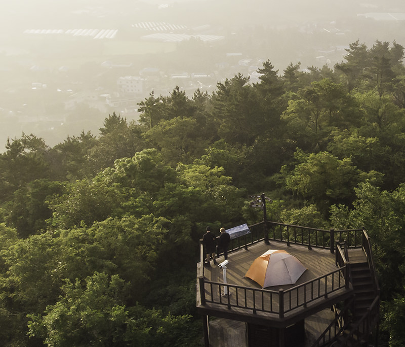 A tent sits on top of the wooden viewing platform on Jeoji Oreum, one of the best places to stay when camping the Jeju Olle Trail