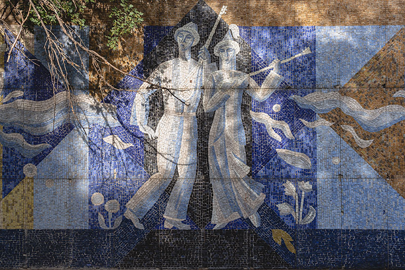 A beautiful example of Soviet-era art and architecture in Almaty - the mosaic of musicians at the Kok Tobe Sanitorium. Two light coloured musicians in traditional dress stand against a blue background.