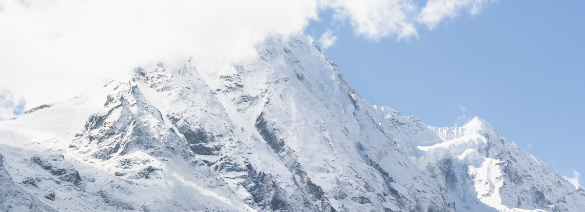 Mountain view with swirling white clouds and blue sky on the Manaslu Circuit and Tsum Valley Trek in Nepal