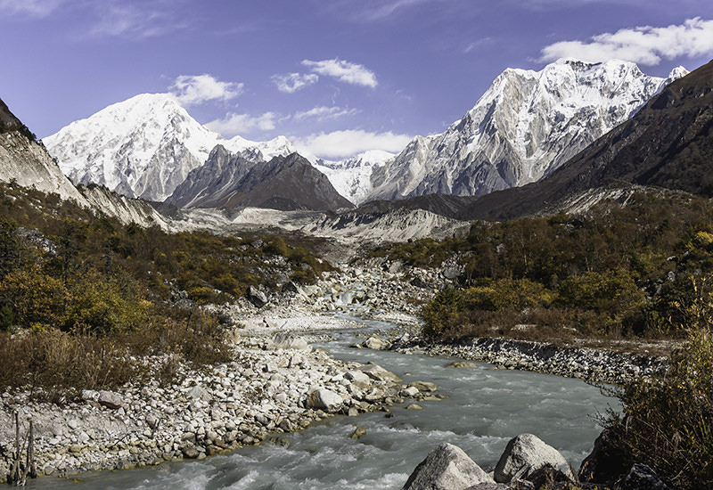 Snowy mountains, milky blue river and bush covered hillsides looking back up towards Bimthang on a sunny morning on the Manaslu Circuit