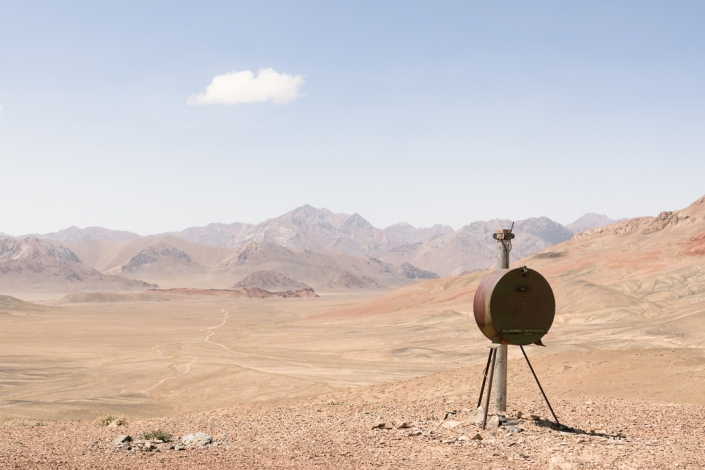 Looking westward from the Shor-bulak Observatory over dry and dusty land with mountains in the distance. The dirt trail below leads south to Jarty Gumbez and north to Murghab.
