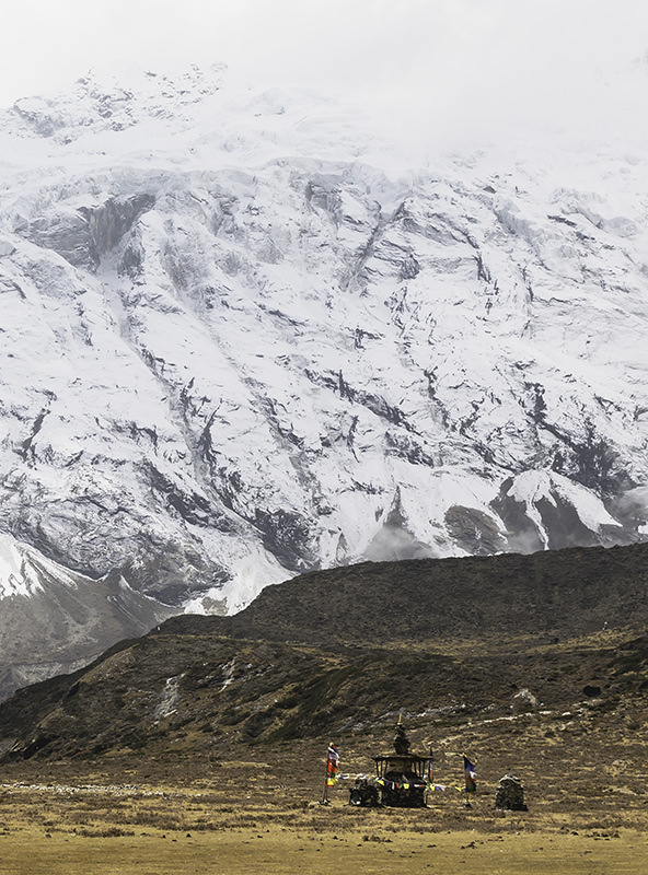 A stupa and prayer flags on high pasture beneath snowy mountains in the Manaslu Region of Nepal