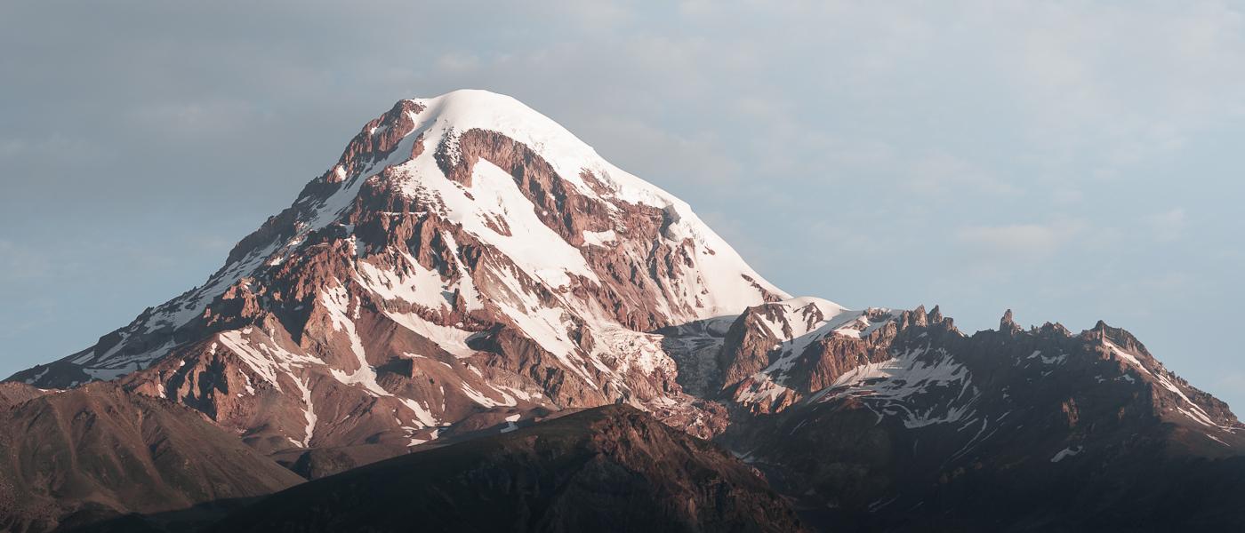 Snow capped Mt. Kazbek shining bright at sunrise, as seen from the town of Kazbegi (Stepantsminda) in northern Georgia
