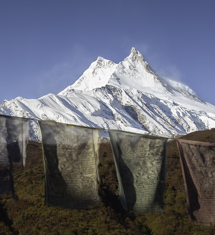 The peak of Mt. Manaslu shining in the sun on a clear morning, with prayer flags in the foreground
