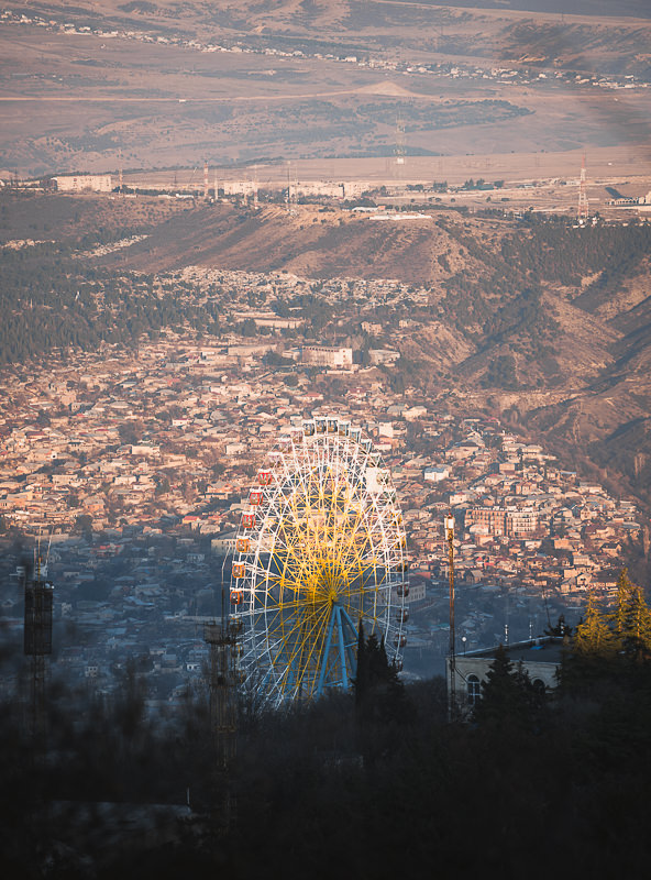 Mtatsminda Park Ferris Wheel is half in shadow, just before sunset in the hills above Tbilisi, Georgia
