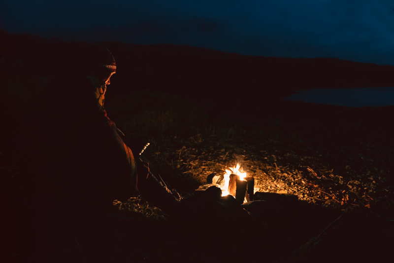 A person sits draped in a blanket next to the golden glow of a campfire as day turns to night on the Isle of Mull.