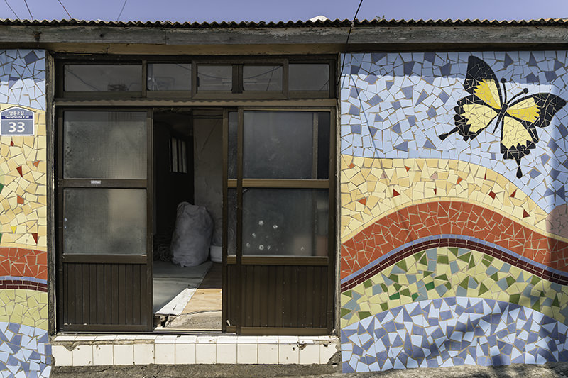 A colourful mosaic wall on the side of a house on Chuja-do