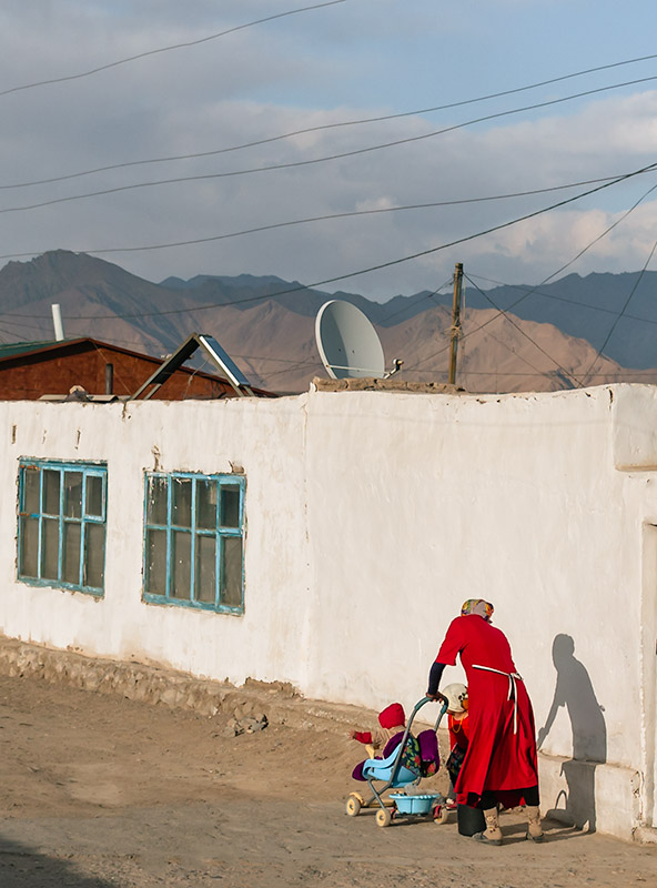 A woman in striking red dress pushing a pram with a baby along a street in Murghab