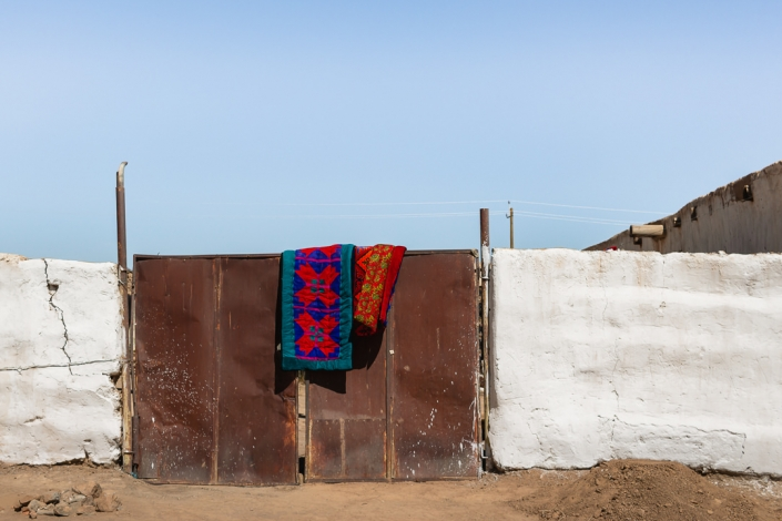 Typically bright blankets put out to air, hanging over a high metal gate in Murghab, Tajikistan.