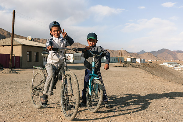 Two boys on their bikes posing for a photo on the streets of Murghab