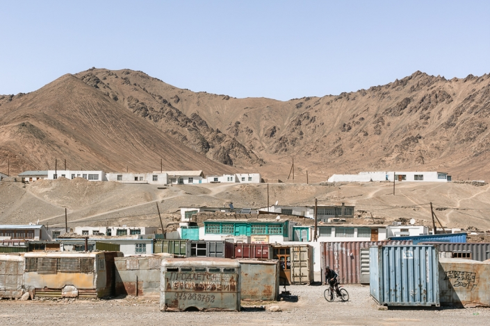 The local market in Murghab, eastern Tajikistan. The market in Murghab is housed in old containers. Houses lie on the hill behind with brown mountains rising behind.