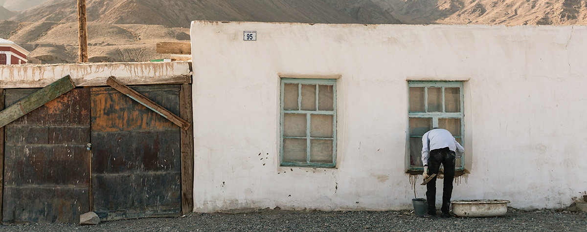 A man is painting a window frame in the whitewashed wall of a house in Murghab in Eastern Tajikistan, one of the larger towns on the Pamir Highway