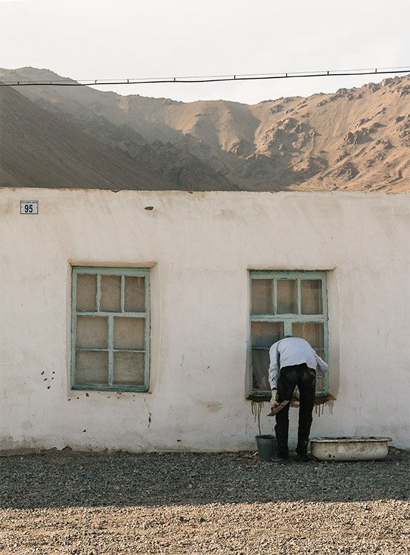 A man painting his window sill green in Murghab
