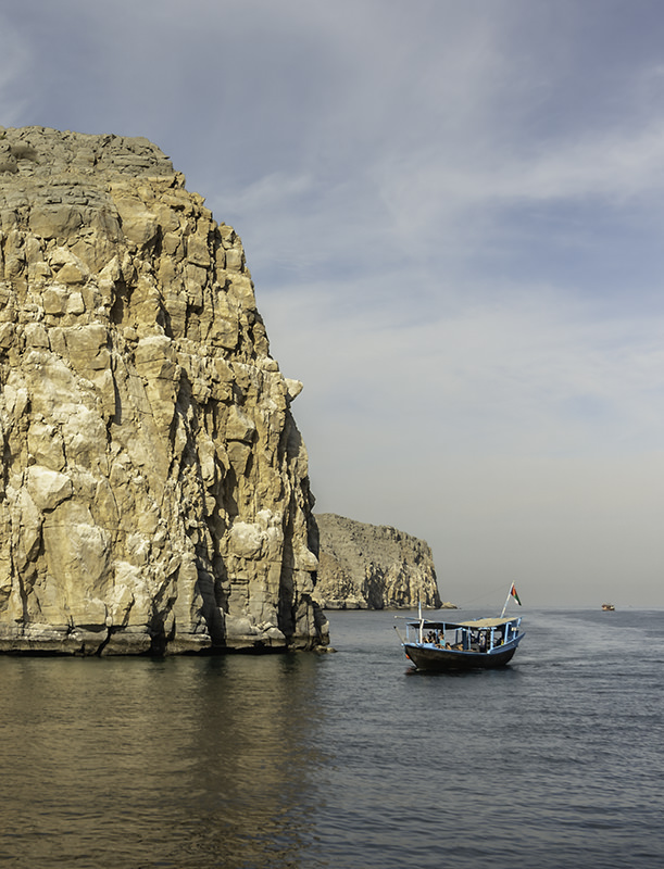 A dhow boat cruises around the rocky sandstone coast in the Musandam Fjords of Oman