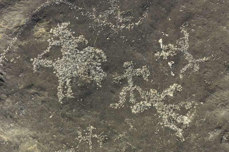 Ancient petroglyphs of human figures on bare rock in the mountains of Musandam, Oman