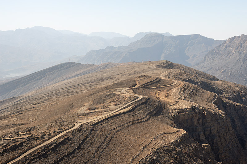 A dirt road snakes through the dry mountains of Musandam, Oman