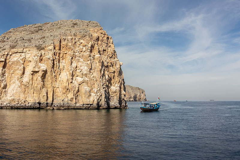 A traditional dhow boat cruising the coast of Musandam. These boats are commonly used for scuba diving in Oman