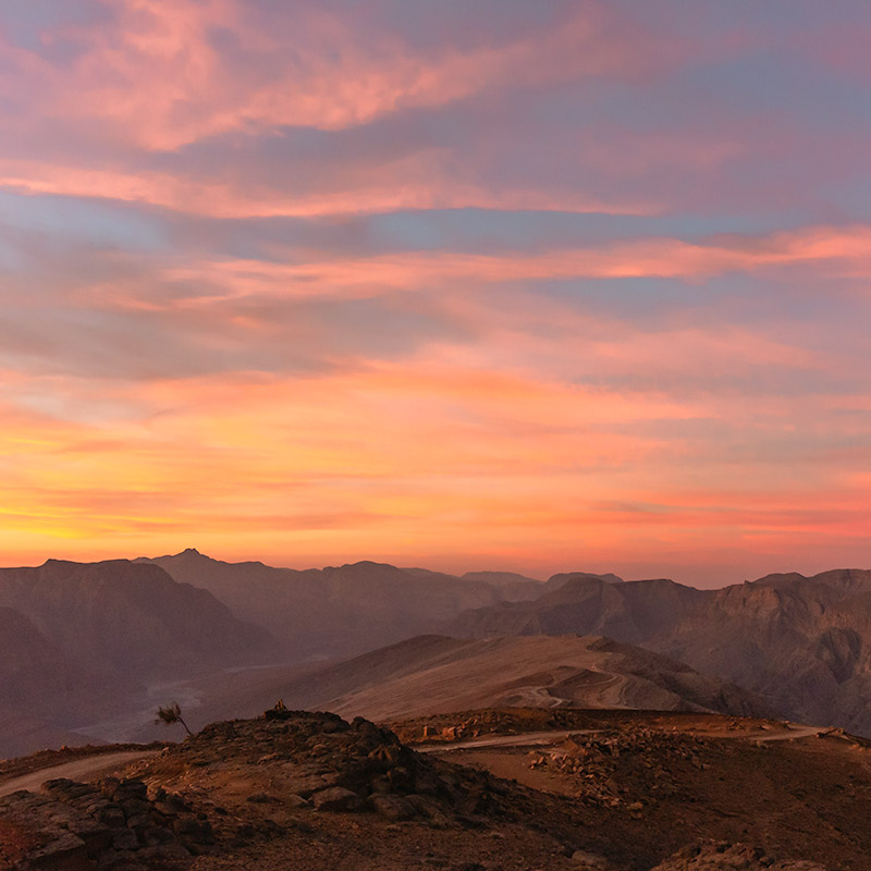A orange, yellow and pink sunrise rises over Wadi Bih in the mountains of Musandam, Oman