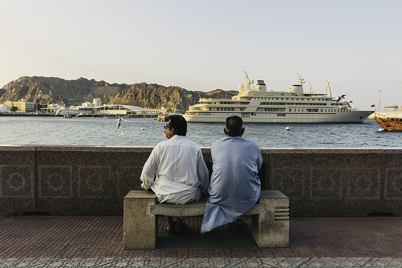 Two men sit on stone bench on the Muttrah Corniche, looking out to the water and enjoying the afternoon sun