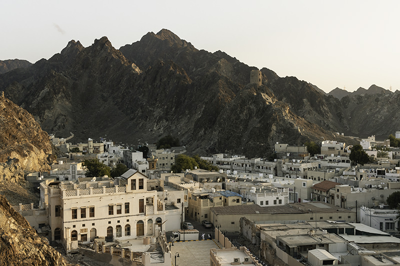 The buildings of backstreet Muttrah with jagged mountains rising behind