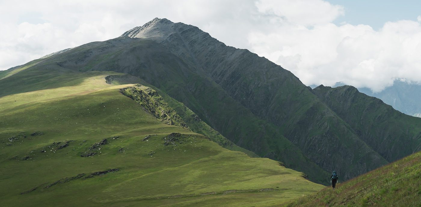 A hiker approaching Nakaicho (Nakle-Kholi) Pass on Day 1 of the Tusheti to Pankisi Valley trek, a great place to stop for lunch and enjoy the mountain views